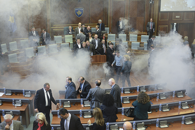 epa04978146 Opposition lawmakers throw tear gas during a session of Kosovo's parliament in Pristina, Kosovo 15 October 2015. Kosovo's opposition political parties protest against the agreements that has been reached during the EU-brokered dialogue with Serbia. EPA/PETRIT PRENAJ