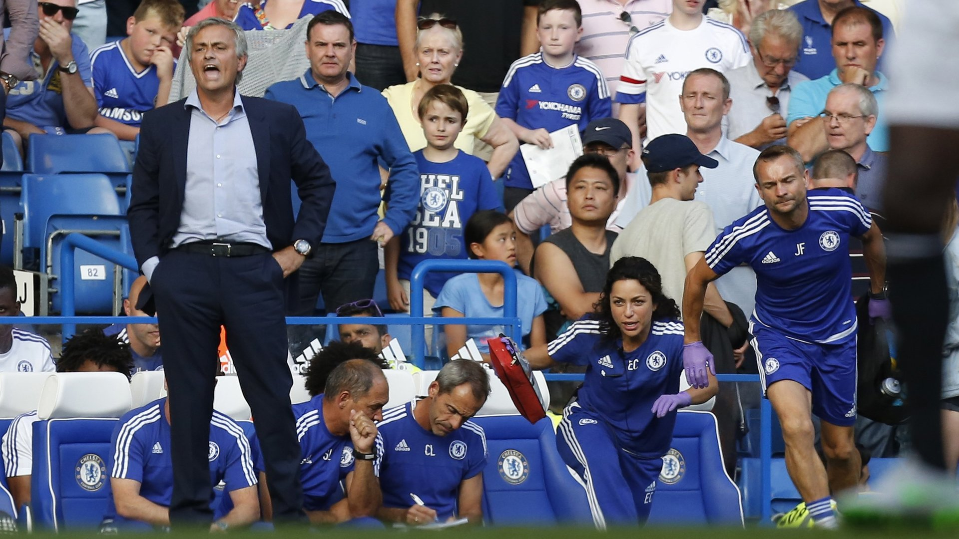 """Chelsea doctor (2R) Eva Carneiro and head physio Jon Fearn (R) leave the bench to treat Chelsea's Belgian midfielder Eden Hazard late in the game as Chelsea's Portuguese manager Jose Mourinho (L) gestures during the English Premier League football match between Chelsea and Swansea City at Stamford Bridge in London on August 8, 2015. Chelsea have sidelined team doctor Eva Carneiro from match-day duties after she fell foul of manager Jose Mourinho, according to British media reports on August 11, 2015. Mourinho criticised Carneiro after she ran on the pitch to treat Eden Hazard in stoppage time of Chelsea's 2-2 draw at home to Swansea City on August 8, saying she did not """"understand the game"""". AFP PHOTO / IAN KINGTON RESTRICTED TO EDITORIAL USE. No use with unauthorized audio, video, data, fixture lists, club/league logos or 'live' services. Online in-match use limited to 75 images, no video emulation. No use in betting, games or single club/league/player publications. (Photo credit should read IAN KINGTON/AFP/Getty Images)"""